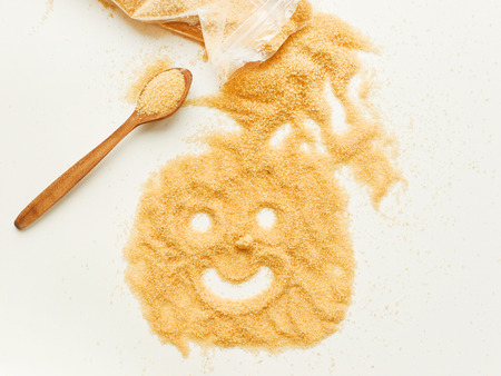 Brown sugar with happy smile face on white wooden background. Shallow dof.