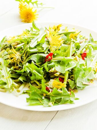 Salad with Dandelion fresh leaves on wooden background. Shallow dof.