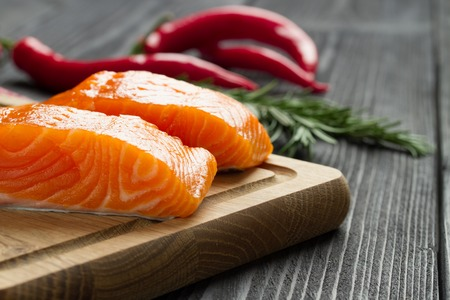 seasonings: Fresh raw salmon fillet on cutting board with seasonings and vegetables.