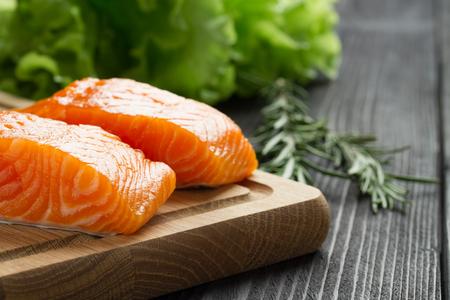 Fresh raw salmon fillet on cutting board with seasonings. Stock Photo