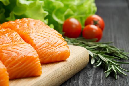 seasonings: Fresh raw salmon fillet on cutting board with seasonings and vegetables.