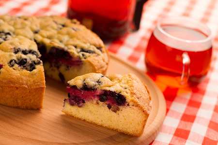 wooden partition: Cut a piece of cake with berries on a wooden chopping board and a checkered napkin with a cup of tea.