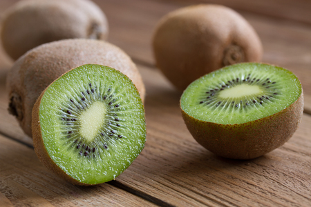 kiwi on a wooden background. in the foreground sliced ??kiwi. close-up 스톡 콘텐츠