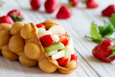 waffles with fruits, strawberries, apple and kiwi on the wooden table