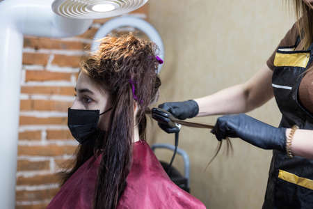 Safe keratin hair straightening from formaldehyde vapors. A client with curly hair is treated with keratin hair straightening under the hood. Hair straightening in the salon