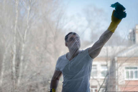 A man washes the window. Spring cleaning.Cleaning company.Cleaning the house.