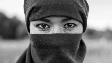 A female terrorist in a dark headscarf, black and white portrait. Shahidka.