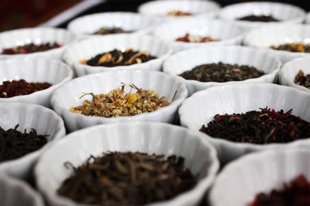 Side view of mixed tea leaves in white cups