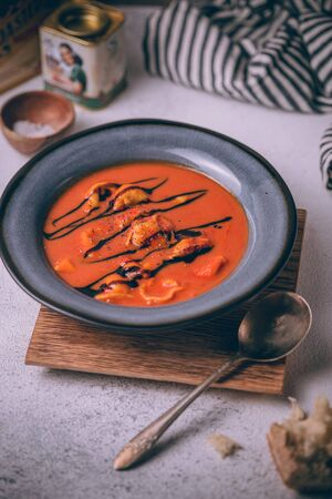 Autumn red tomato cream soup with homemade cheese tortellini and topped with balsamic reduction. Soup bowl in rustic style. 免版税图像