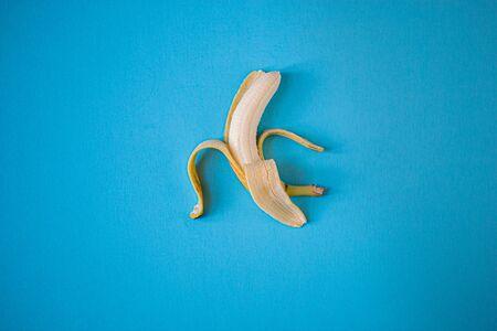 Single yellow banana on a blue background