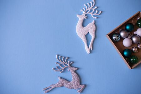 Christmas mood flat lay. Happy New Year flat lay on the paper. Sparkling silver and white deer ornaments on blue paper.