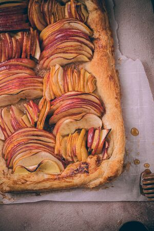 Autumn apple puff pastry tart with cinnamon spice and honey drizzle. Comfort Fall baking food. Фото со стока
