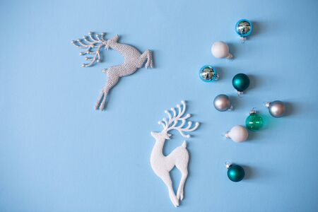Christmas mood flat lay. Happy New Year flat lay on the paper. Sparkling silver and white deer ornaments on blue paper. Christmas ball ornaments