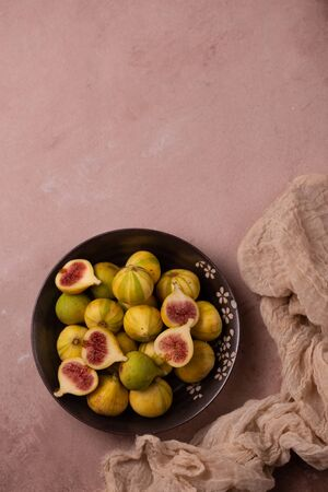 Juicy fresh tiger figs in bowl on dust pink table. 免版税图像