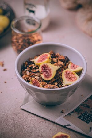 Domowa zdrowa granola ze świeżymi figami i miodem skropiona w misce śniadaniowej na różowym stole. Zdjęcie Seryjne