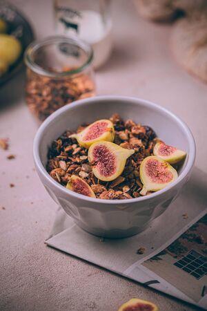 Granola sain fait maison avec des figues fraîches et de la bruine de miel dans un bol de petit-déjeuner sur une table rose. Banque d'images