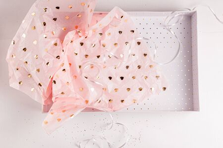Pastel pink gift paper with golden hearts in white present box. Gift wrapping for special occasion. Valentine's Day, Birthday Party, Wedding Anniversary, Mother's Day present. Handmade gift