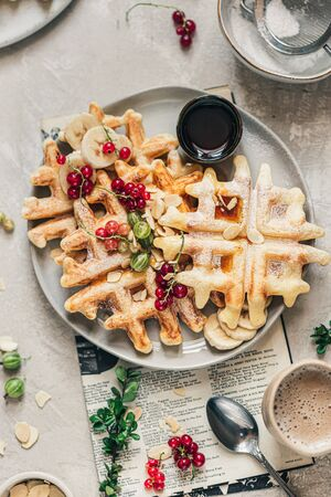 Crispy belgian waffles with red currants, gooseberry, maple syrup and powdered sugar on the grey ceramic plate