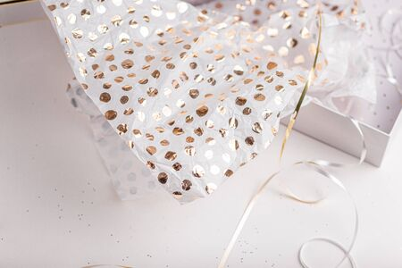 Gift wrapping. Festive wrap paper for Christmas, New Years Eve celebration. White, golden, silver festive colors. Holiday season. Handmade gift box packing. Birthday party celebration.