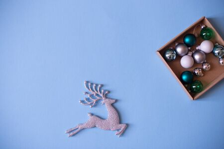 Christmas mood flat lay. Happy New Year flat lay on the paper. Sparkling silver deer ornaments on blue paper. 免版税图像