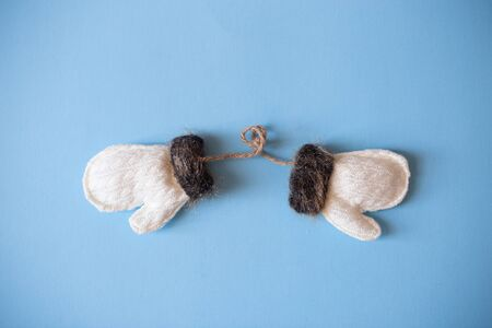 Christmas mood flat lay. Happy New Year flat lay on the paper. White woolen mittens with brown fur on blue paper.