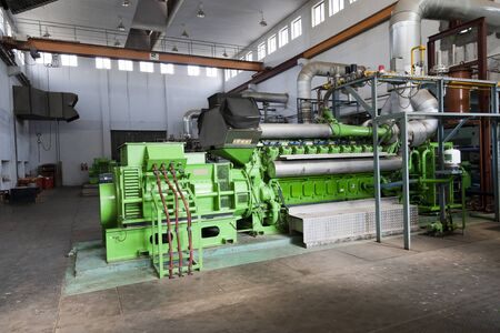 heavy risk: huge industrial standby dieasel generator at a power generation plant in a textile factory. Stock Photo