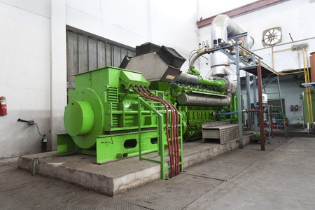 generator: huge industrial standby dieasel generator at a power generation plant in a textile factory. Stock Photo