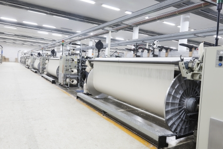 textile industry: A row of textile looms weaving cotton yarn in a textile mill. Stock Photo