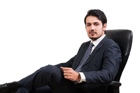 indian business man: portrait of a confident Arab businessman sitting on a chair, biracial businessman isolated on white