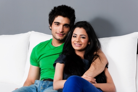 married together: young happy indian couple relaxing on the sofa, happy multi ethnic couple relaxing on white sofa Stock Photo