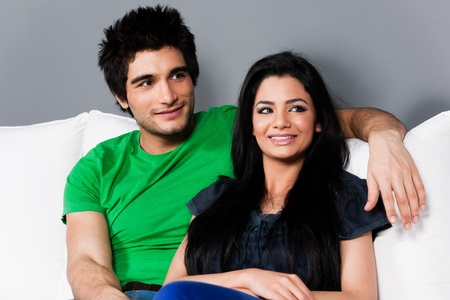 young happy indian couple relaxing on the sofa, happy multi ethnic couple relaxing on white sofa photo