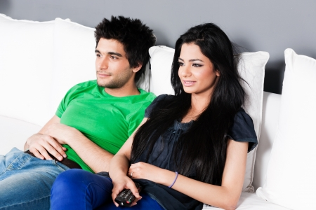young and happy ethnic couple relaxing on the sofa and watching movie, young couple watching movie   photo