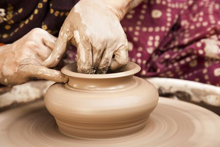 female potter s hands shaping up the terracotta clay pot on wheal   photo