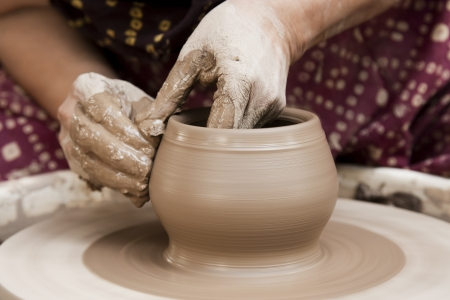 female potter s hands shaping up the terracotta clay pot on wheal   Stock Photo