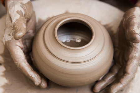 clay pot: female potter s hands shaping up the terracotta clay pot on wheal   Stock Photo