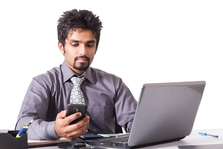 young indian businessman using cell phone while working on the laptop, Inidan businessman working on the laptop isolated on white photo