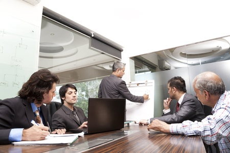 sala de reuniões: Homem de negócios que dá a apresentação de um grupo de grupo racial de vários colegas, um grupo de empresários diversed.