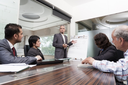 young businessman giving presentation to a group of multi racial group of colleagues, a group of diversed businessmen.