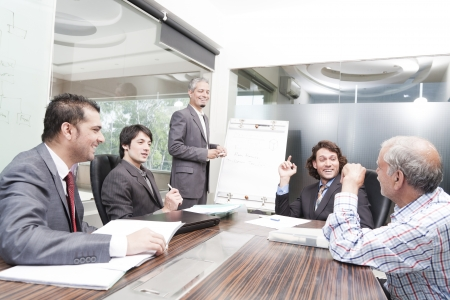 sala de reuniões: Homem de neg?cios que d? a apresenta??o de um grupo de grupo racial de v?rios colegas, um grupo de empres?rios diversed.