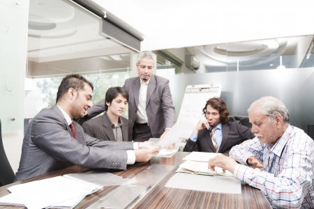 young businessman giving presentation to a group of multi racial group of colleagues, a group of diversed businessmen. Stock Photo - 14273291