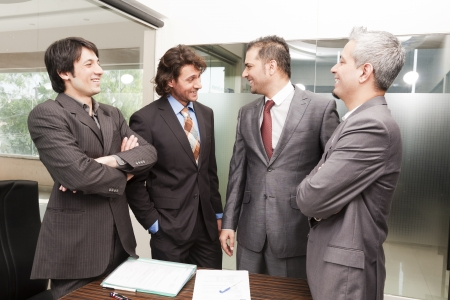 mixed race ethnicity: Group of happy businessmen having a casual discussion after the official meeting.
