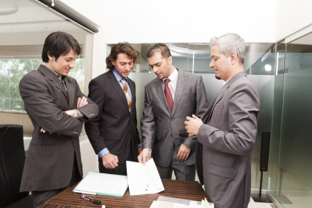 Group of happy businessmen having a casual discussion after the official meeting. photo