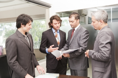 Boardroom meeting: Group of happy businessmen having a casual discussion after the official meeting.