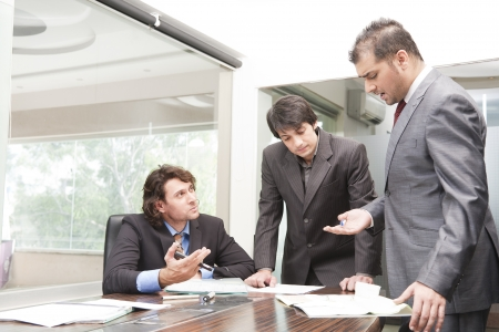 Boardroom meeting: group of young businessmen having a serious and intense discussion in the business meeting