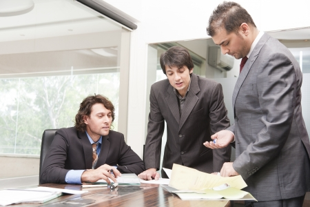 group of young businessmen having a serious and intense discussion in the business meeting  photo