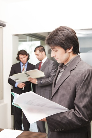 portrait of a young asian businessman with his colleagues in background photo