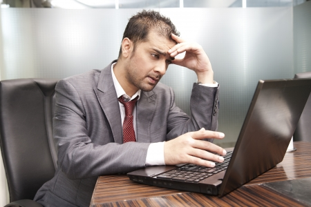 american banker: close up of a young businessman getting frutrated while working on the laptop  Stock Photo