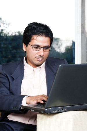 thoughtful Indian businessman working on laptop, businessman lost in deep thoughts photo