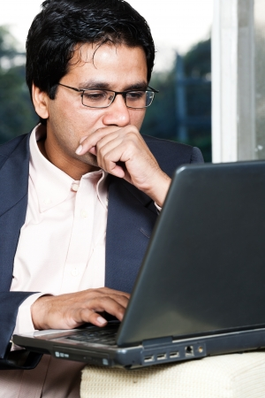 deep thought: thoughtful Indian businessman working on laptop, businessman lost in deep thoughts