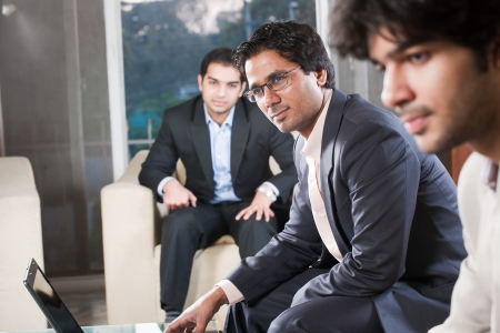 education: confident indian businessman with his colleagues in the background Stock Photo